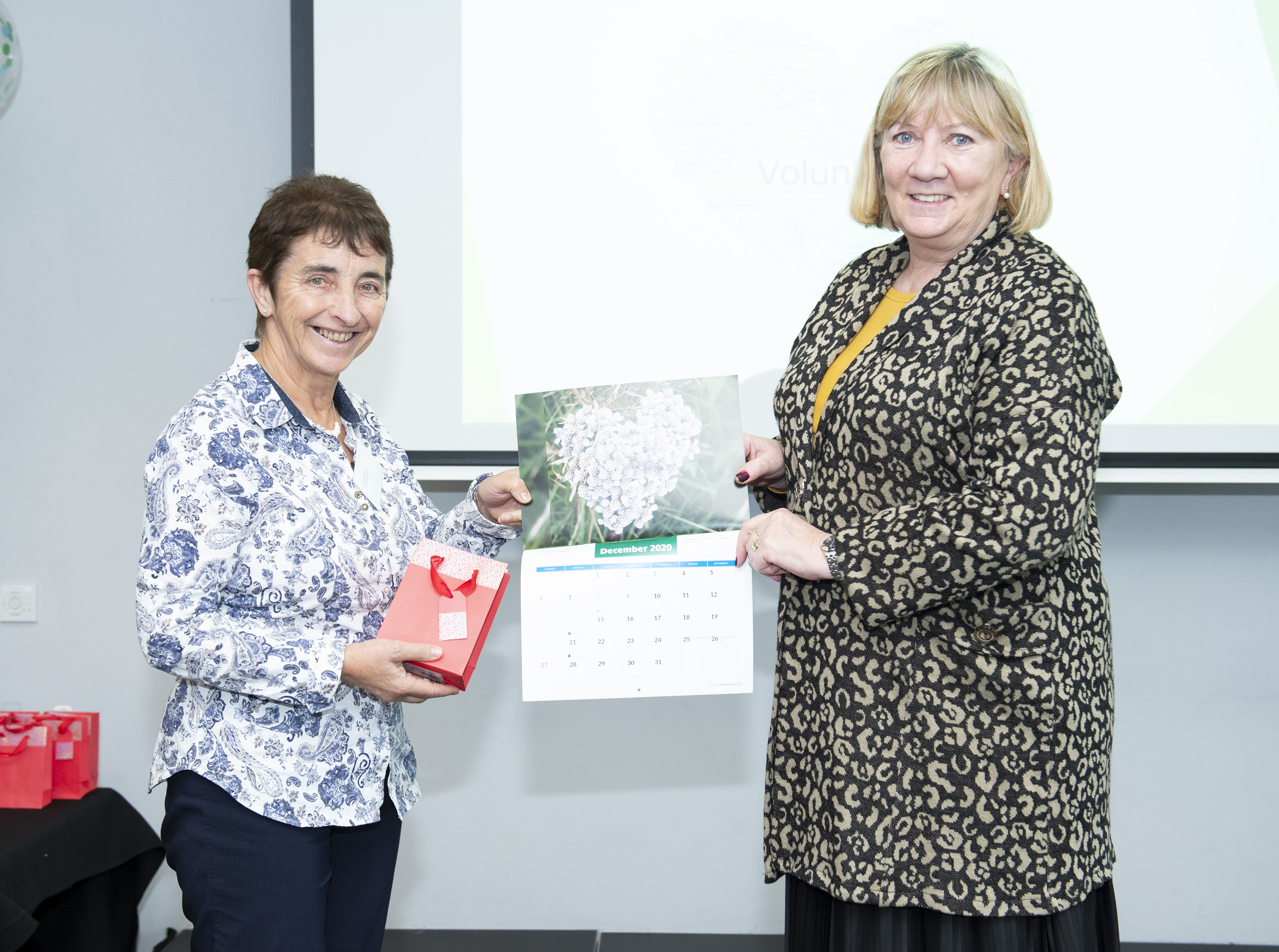 Angela Black, Chief Executive presents Teresa Butler, volunteer with North Munster CIS with her Calendar 2020 prize.